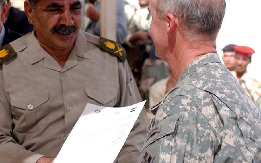 A handshake seals the deal between Maj. Gen. Hussein Al-Ghazali , left, and Col. John Tully after the two signed documents officially handing over Forward Operating Base Duke to Iraqi security forces.