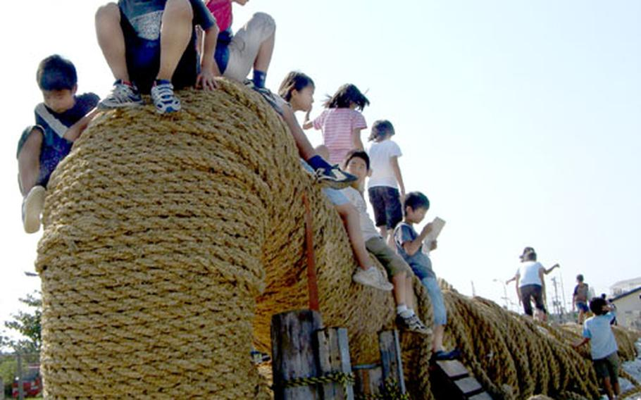 Japanese school children play on the Naha Great Tug-of-War rope during a field trip to the Naha Military Port, where the 10-foot high, 660-foot long rope is constructed each year.