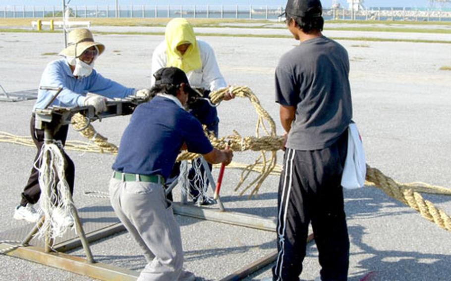 Jiro Uehara, a fisherman who takes time away from the sea to help build the tug-of-war rope, cuts a completed rope from the machinery used to twist it together.