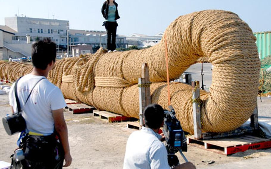 A Japanese broadcast journalist files her report about the crafting of the Naha Great Tug-of-War rope as she walks across the top of it. The contest draws a crowd of more than 250,000 each year.
