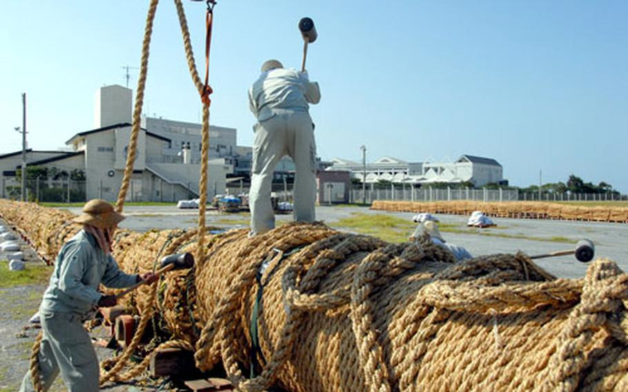 Workers use mallets to soundly secure the pulling ropes into place on one of the 330-foot sections of the tug-of-war rope.