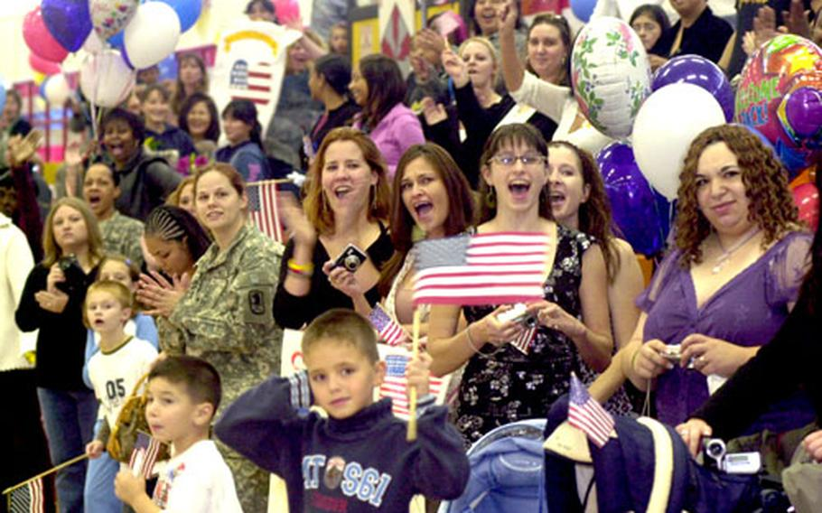 Family members and friends react as the soldiers of the Darmstadt, Germany-based 22nd Signal Brigade march into the gym at Cambrai-Fritsch Casern following their return from Iraq on Wednesday.