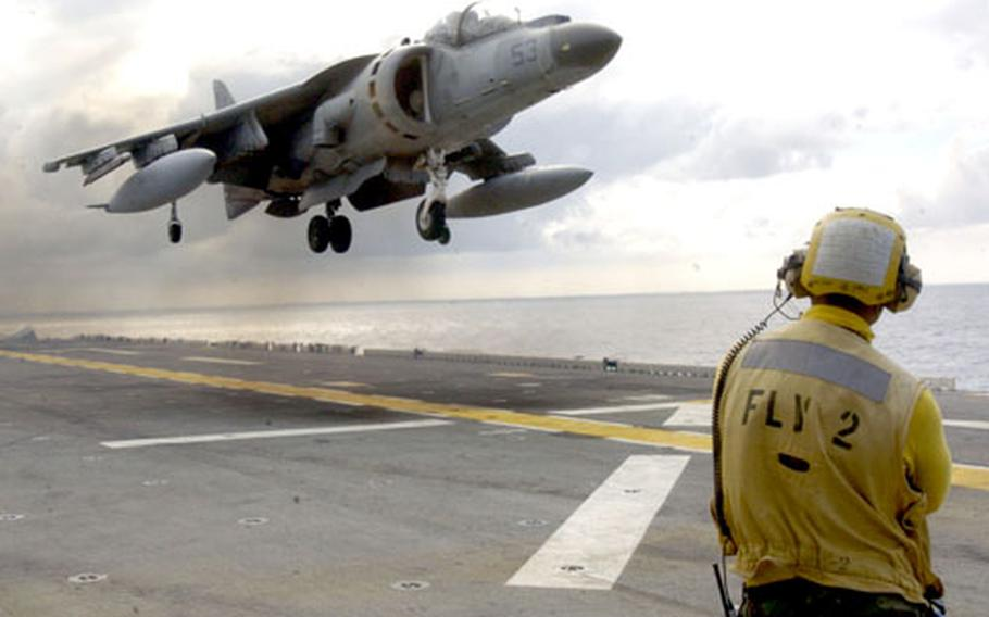 Navy Airman Isaac Berwick watches a AV-8B Harrier land on the flight deck of the forward-deployed amphibious assault ship USS Essex on Saturday. The Harrier is part of the 31st Marine Expeditionary Unit's Marine Attack Squadron out of Iwakuni, Japan.