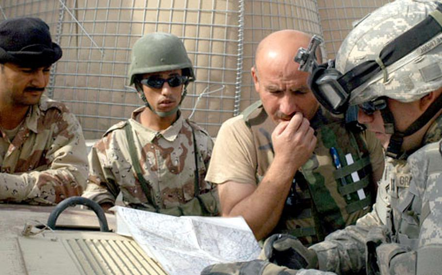 On the way out to perform reconnaissance in a little-patrolled area south of Kirkuk Tuesday, Capt. Jonathan Graebener, commander of Company A, 2nd Battalion, 35th Infantry Regiment, 25th Infantry Division, far right, maps out a plan with Iraqi army members.