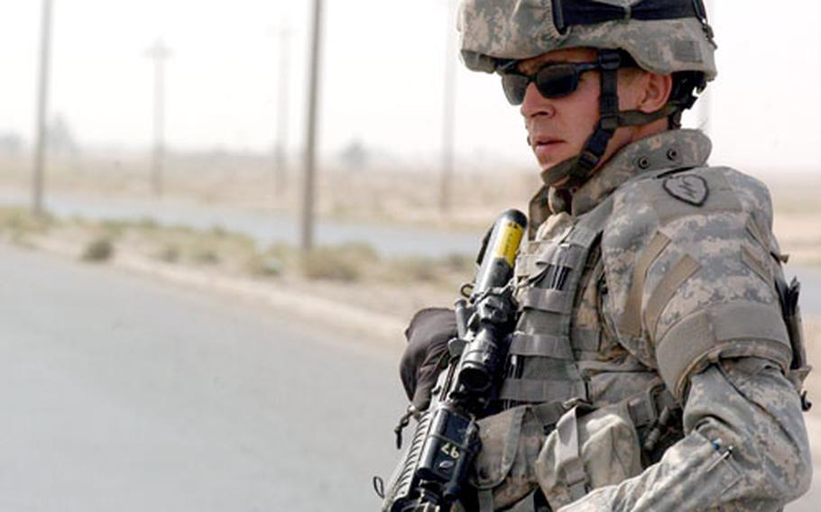 Pvt. 1st Class Terrance Fusek from Company A, 2nd Battalion, 35th Infantry Regiment hailing from Schofield Barracks, Hawaii, scans for the triggerman in a roadside bomb explosion that hit a Humvee just in front of him Tuesday on Route Clemson south of Kirkuk.