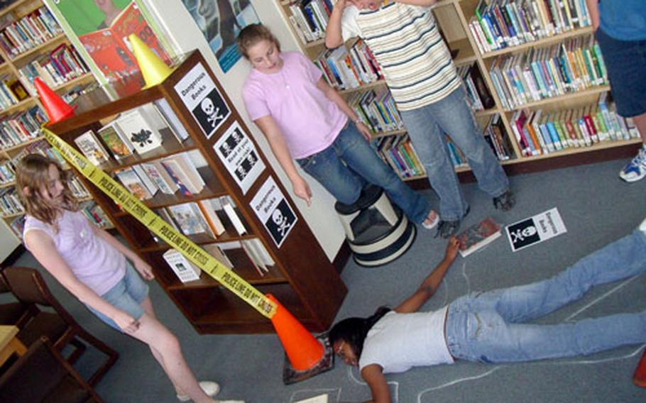 """Students from 7th and 8th grade at the consolidated schools at Marine Corps Air Station Iwakuni """"react"""" to a student floored by the """"Thought Police"""" for reading a challenged book as part of the weeklong banned-book week."""
