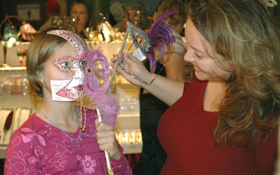 Nine-year-old Ellen Haapoja tries on an Italian mask as her mom, Jennifer Haapoja, looks on.