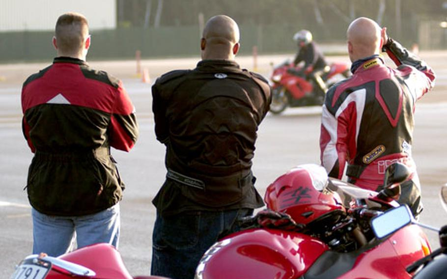Students watch as Al Manglicmot, a motorcycle safety instructor for the U.S. Army Garrison Kaiserslautern safety office, demonstrates navigation last month at the motorcycle safety course at Kapun Air Station.