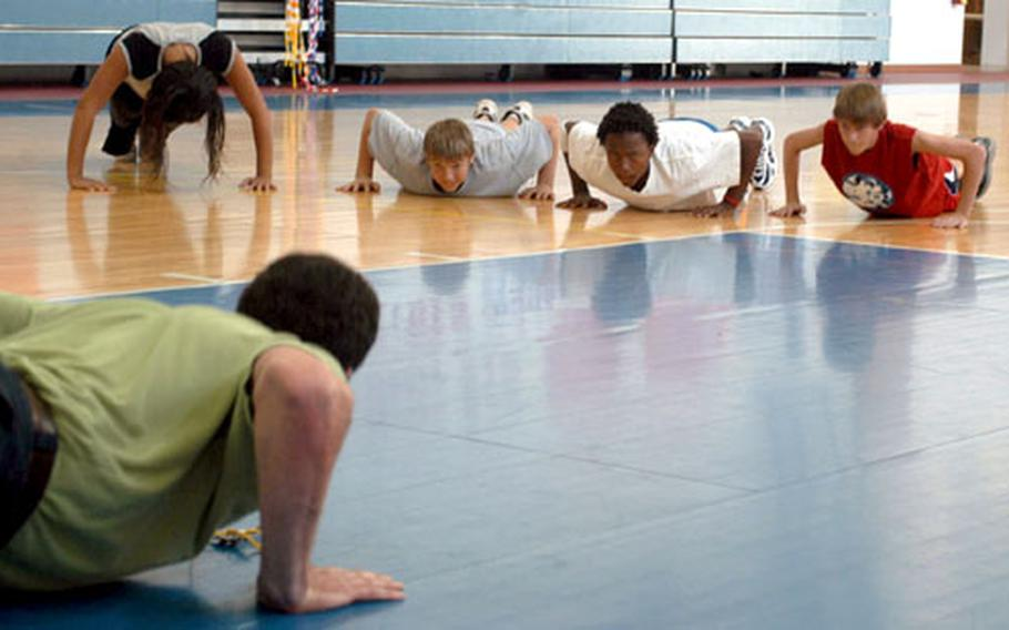 Physical education instructor Tim Morse, left, leads his eighth-grade class by doing push ups in the Aviano High School gymnasium. Morse instructs the students three times a week, with classes lasting 90 minutes each.