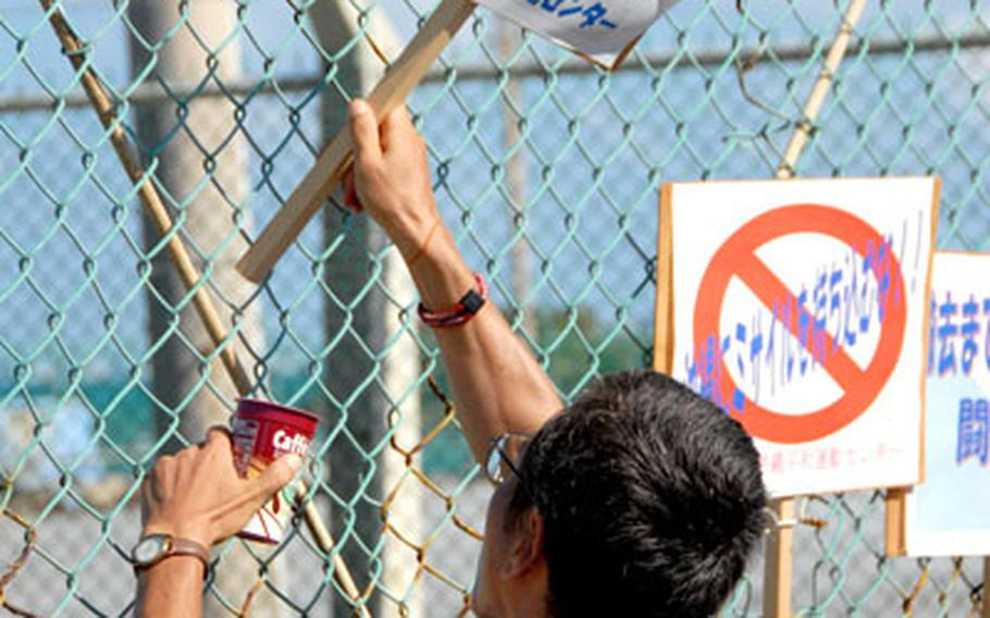A protester hangs a sign on the fence at Tengan pier Monday afternoon. The group had been protesting the likely arrival of 24 Patriot missiles since Sunday night.