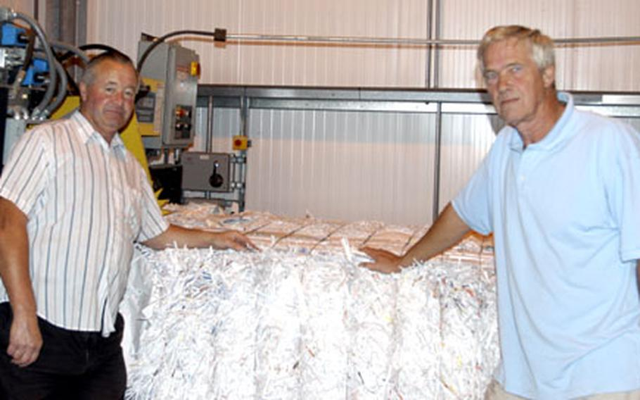 Brian Giles, left, and Rod Barrett, stand next to a bundle of shredded paper set to be recycled. The two British men work at the RAF Lakenheath recycling center as employees of the Ministry of Defence.