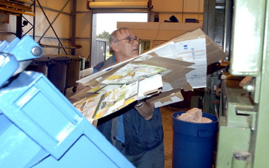 Robert Pool loads a pile of cardboard into a compactor at the RAF Mildenhall recycling center.