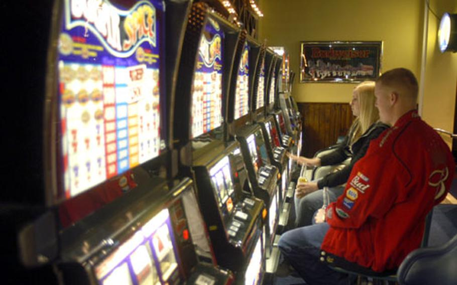 Senior Airman Beau Ross and his wife, Amy, try their luck at one of the 30 gaming machines found at the Galaxy Club.