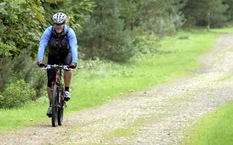 A bicyclist enjoys a morning ride along a path near the High Lodge inside the Thetford Forest.