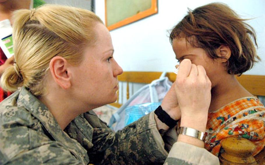 Sgt. Katie Faint examined a little girl's eye during a recent medical operation in Baghdad.