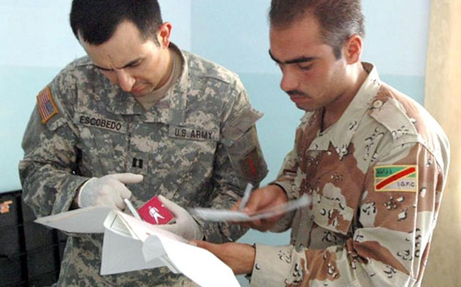 Dr. (Capt.) David Escobedo (left) and Iraqi army medic Sadoon Karim look at drug information during a recent medical operation in Baghdad. Karim was one of three Iraqi army medics who participated in the operation. An Iraqi army doctor did not arrive until five minutes before the close of the operation.