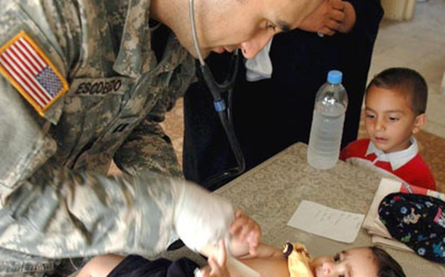 Dr. (Capt.) David Escobedo tended to patients big and small during a clinic in Baghdad late last month.
