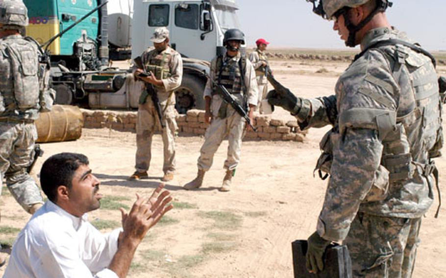 Staff Sgt. Albert Buchinski from Morris, Ill., talks with an Iraqi man in a small town south of Forward Operating Base McHenry where U.S. and Iraqi military members were searching for a notorious roadside bomb maker Sunday. The man pictured was not taken into custody.