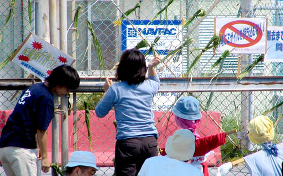 """About 75 protesters continue to block the gate to Tengan Pier on Tuesday, vowing to remain encamped to prevent the transfer of Patriot missiles from a ship to Kadena Air Base. They began their vigil Sunday. The strips of grass tied to the gate are """"sans,"""" the traditional Okinawan taboo sign to ward off evil spirits."""