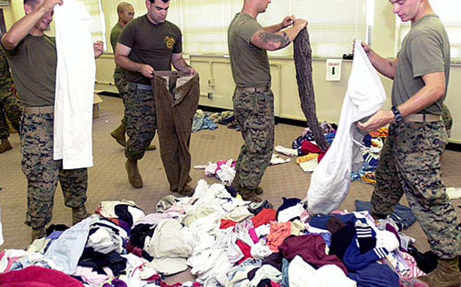 Marines and sailors sort donated clothes for the Blue Green Gift Box Initiative at Camp Hansen.