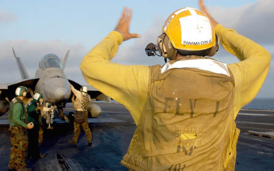 Airman Brian Kuhaneck, aircraft director on catapult 2 aboard the USS Enterprise, directs an F/A-18 Super Hornet getting ready to launch from the carrier on its way to Afghanistan.