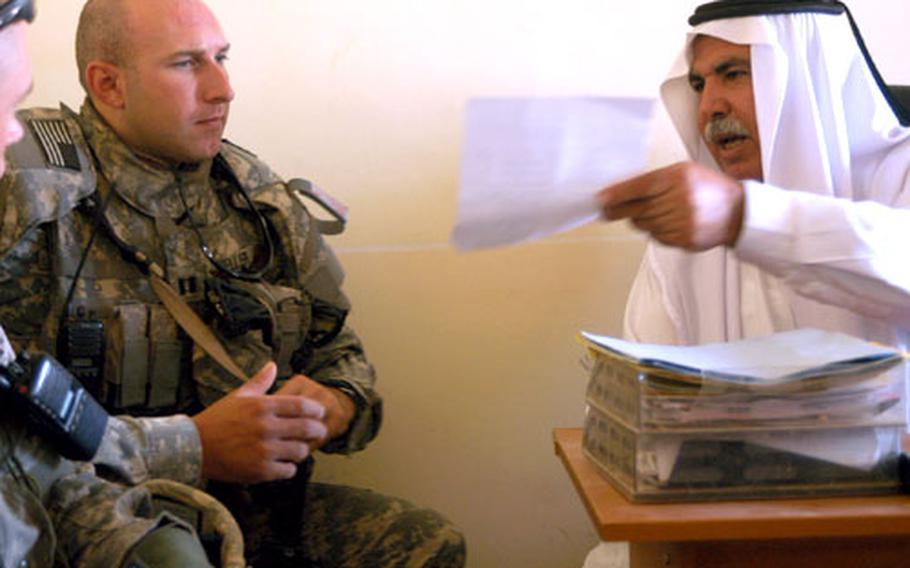 """Capt. Roland Keller, left, from Company D of the 2nd Battalion, 27th Infantry Regiment """"Wolfhounds,"""" looks over some paperwork Monday with Mohammed Ahmad Hussain, mayor of the town of Riyadh, at a weekly city council meeting."""