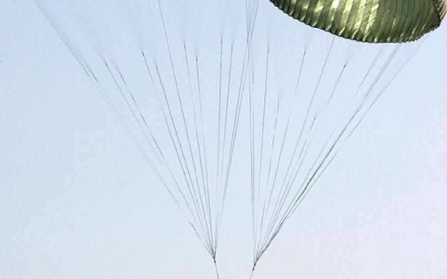A Humvee parachutes to the ground after being dropped from the back of a C-130 transport aircraft.