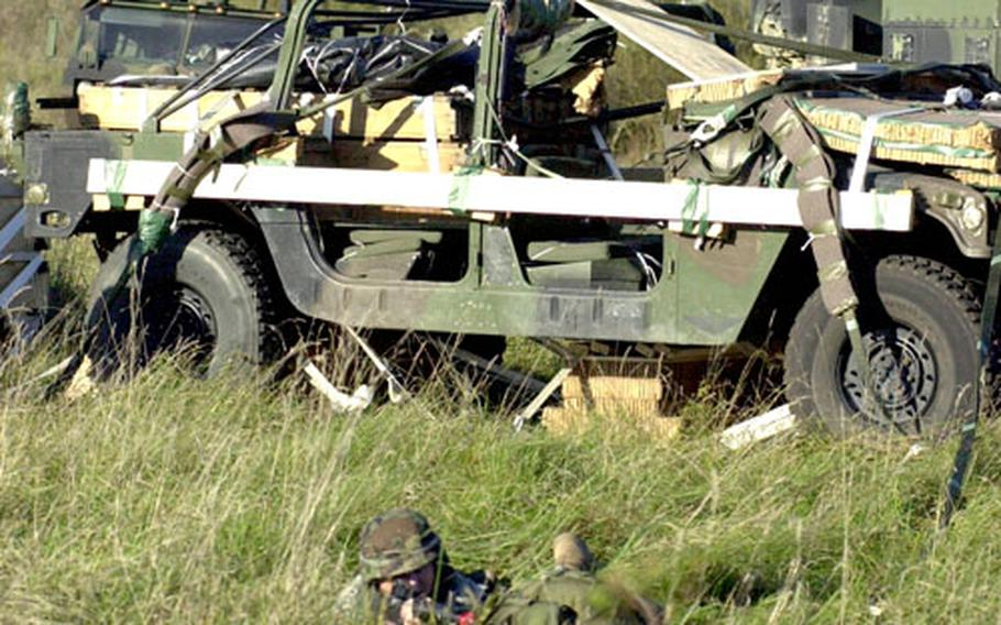 Staff Sgt. Justin Merritt, 33, of Marion, Ill. posts guard on the Humvee that his unit, the 5th Quartermaster Detachment, dropped from a C-130 transport aircraft over Hohenfels.