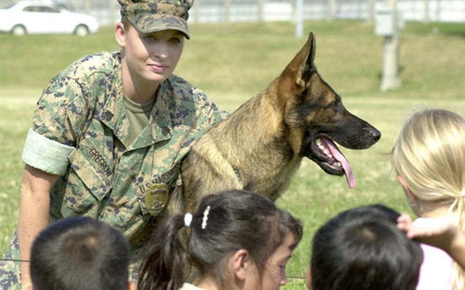 Sgt. Sara Gregrow, 23, hugs her partner Meister, a two-year-old German shepherd, as she answes questions Thursday about their jobs as a military working dog team during a demonstration for students at Bechtel Elementary School on Camp McTureous, Okinawa. Gregrow said that seeing a similar demonstration when she was 12 inspired her to become a military-working-dog handler.