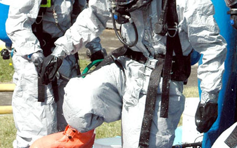 A member of a Japanese hazardous material team steps out of a decontamination shower during the Kanto Plain-wide exercise at Camp Zama.