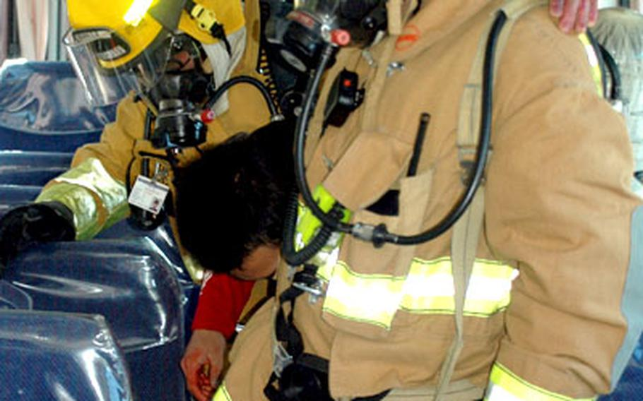 Two Japanese firefighters evacuate a victim from a bus crash during the exercise Thursday at Camp Zama.