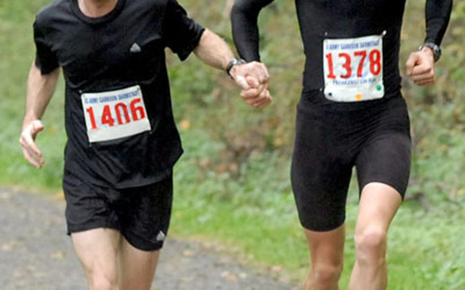 Neil Hersey, left, and Benjamin Martinelli run the final yards of the Frankenstein Castle Run hand-in-hand, with Martinelli narrowly winning the 13-kilometer race. Besides finishing second, Hersey was the top finisher in his age class.