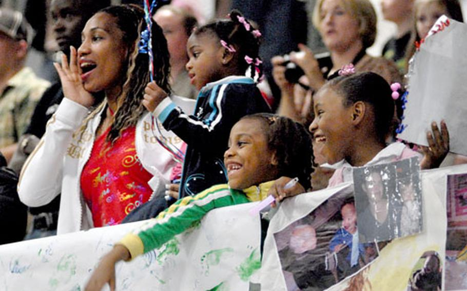 """Summer Covin, along with her daughters, Queen, Sahryia and Johnaya, cheer as members of the 226th Medical Battalion, Logistics """"Forward"""" march into formation at the Miesau Army Depot gym late Thursday night after returning home from a one-year deployment to Balad Air Base, Iraq, on Thursday."""