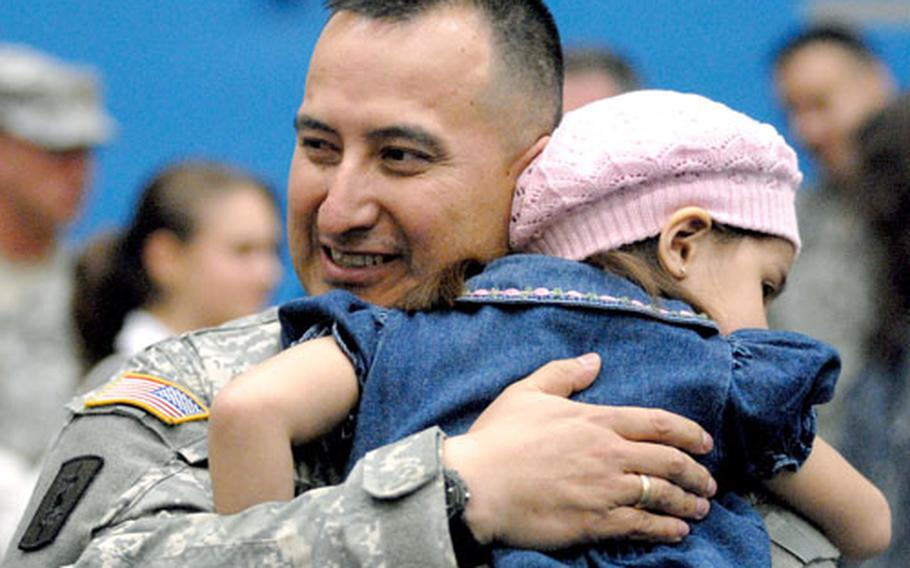 Staff Sgt. Wilmer Tapia enjoys a hug from daughter, Melonie, after returning home from a one-year deployment to Balad Air Base, Iraq, on Thursday.