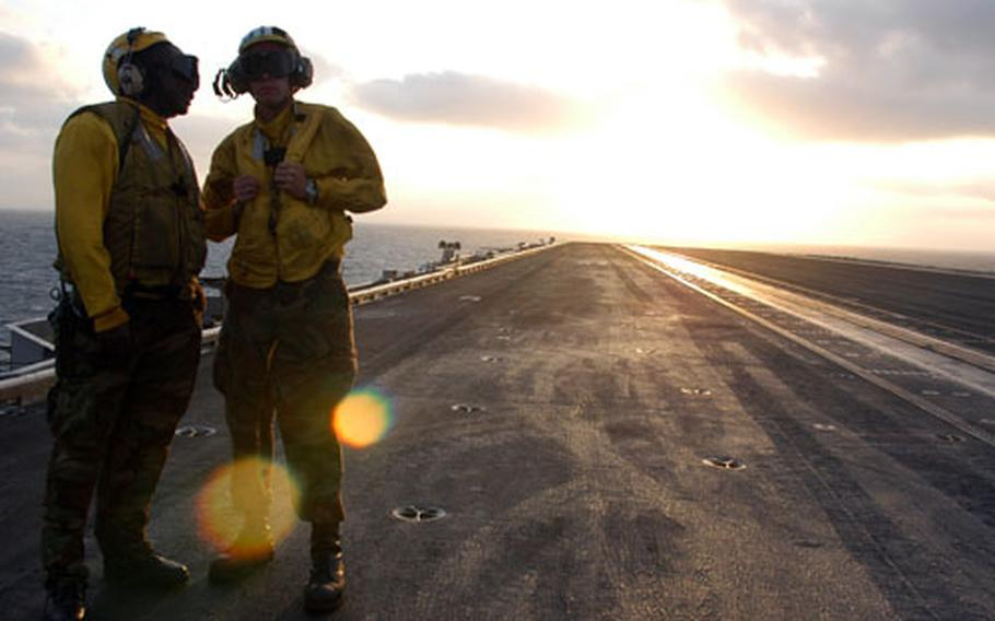 As sunset approaches, Airman Stuart Barksdale, right, and Airman Terry Keyes chat on the flight deck of the USS Enterprise.