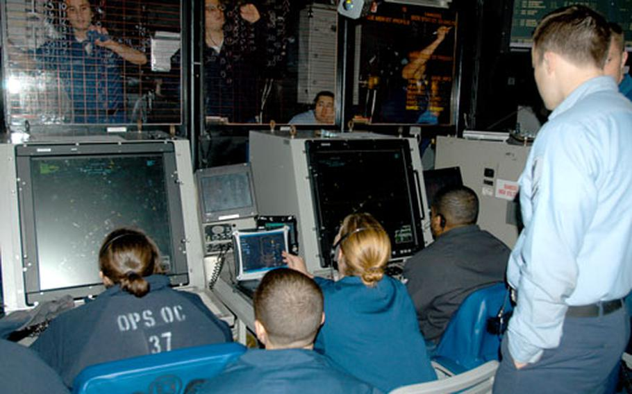Petty Officer 2nd Class Samuel Hughes, Carrier Air Traffic Control Center supervisor, looks over the shoulders of air controllers at a radar screen as aircraft land at night on the USS Enterprise.