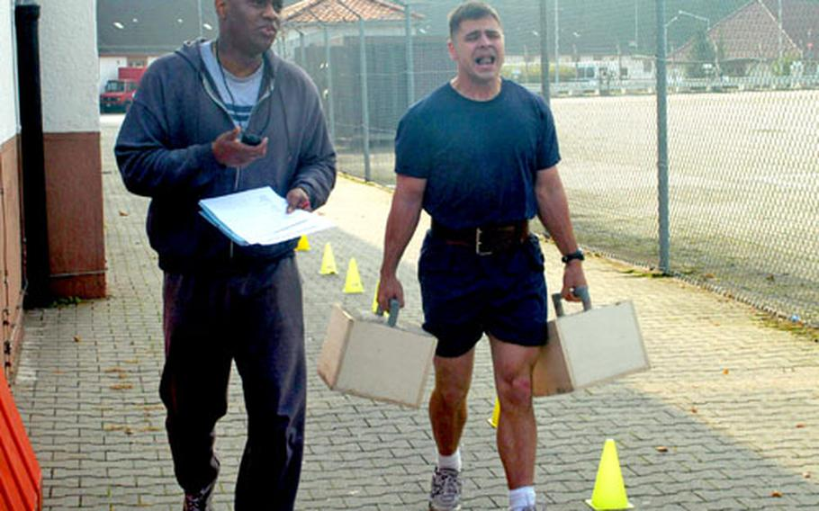 It's no stroll in the park. Capt. Jake Jacobson, right, walks through the pain Saturday carrying concrete blocks at the USAG Darmstadt Strongman competition as fitness coordinator Brian Morgan watches his time and provides encouragement.