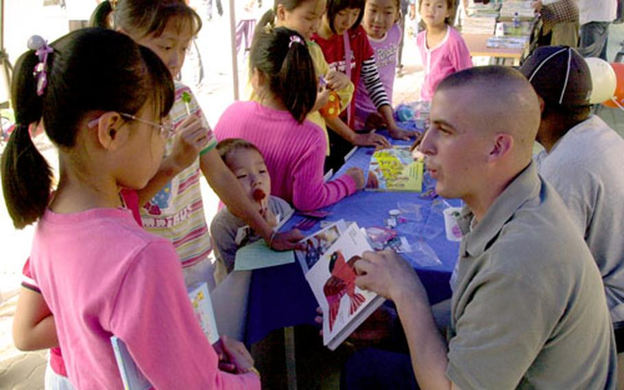Sgt. Scott Ramey whistles like a bird while teaching South Korean children English during a volunteer fair in Dongducheon, South Korea, on Saturday. Twenty-one soldiers from the 2nd Infantry Division's 2nd Battalion, 9th Infantry volunteered to spend days on both weekends manning the booth on behalf of United Service Organizations.