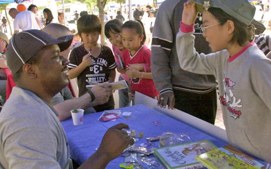 Staff Sgt. Bryan Stewart teaches South Korean children English during a volunteer fair in Dongducheon, South Korea, Saturday.