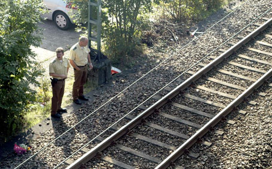 German  survey the scene where two American service women were fatally struck by a train Saturday. The train, a regional express, was not scheduled to stop at the station in Neckarhausen and struck the soldiers despite emergency measures taken by the train's driver to alert them and stop the train.