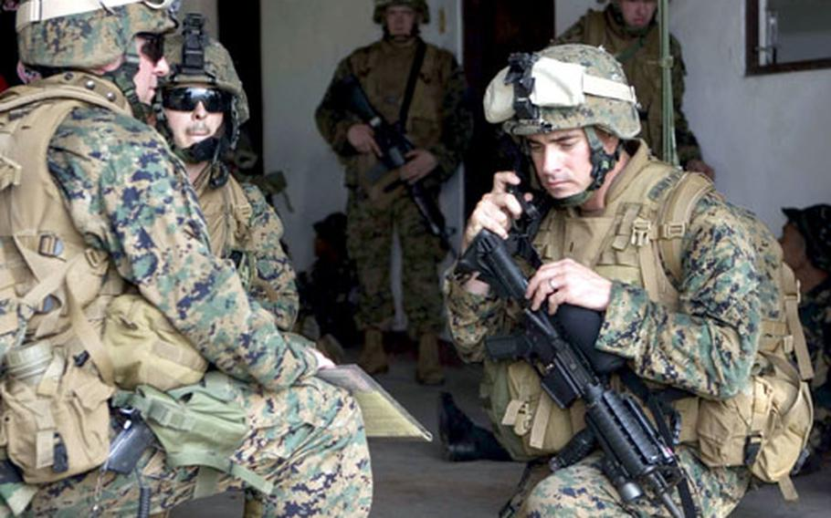 U.S. Marines and sailors from Battalion Landing Team 1st Battalion, 5th Marine Regiment of the 31st Marine Expeditionary Unit, await extraction after completing a helicopter-borne raid at Basa Air Base in the Philippines Sunday.