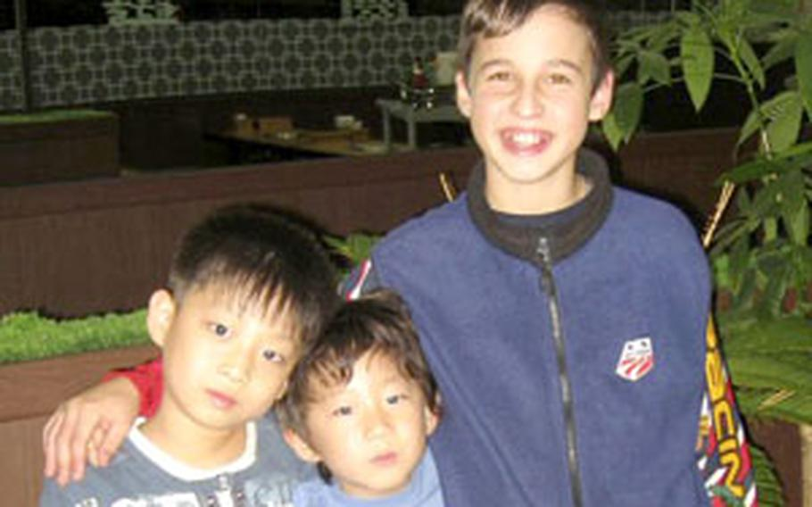 Adam Budge, 13, poses with Park Jung-hoon (center), who lay lifeless at the bottom of a swimming hole near Osan Air Base in August until Budge retrieved him after a series of dives.