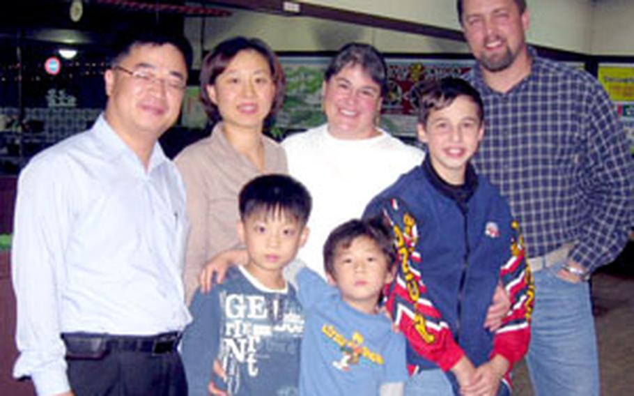 Adam Budge, 13, second from right, stands with him parents, Park Jung-hoon and Park's family at a restaurant in Osan City last week. Behind Budge are his parents Heather and Richard. Park Jung-hoon is at center with his arm around his elder brother. His parents are at left.
