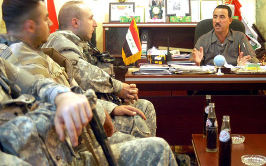 Abdul Kareem Ali, right, mayor and overall town manager of Multaka who is also known as Abu Saif, talks with members of Company D from the 2nd Battalion, 27th Infantry Regiment based at Forward Operating Base McHenry in a weekly meeting.