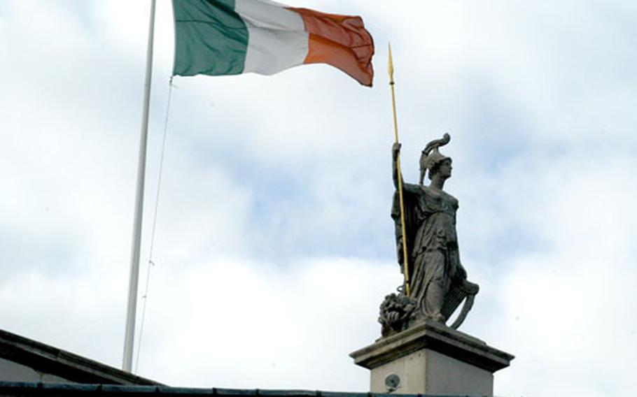 A Roman centurion stands before the Irish flag atop the main post office building on O'Connell Street, in the heart of Dublin.