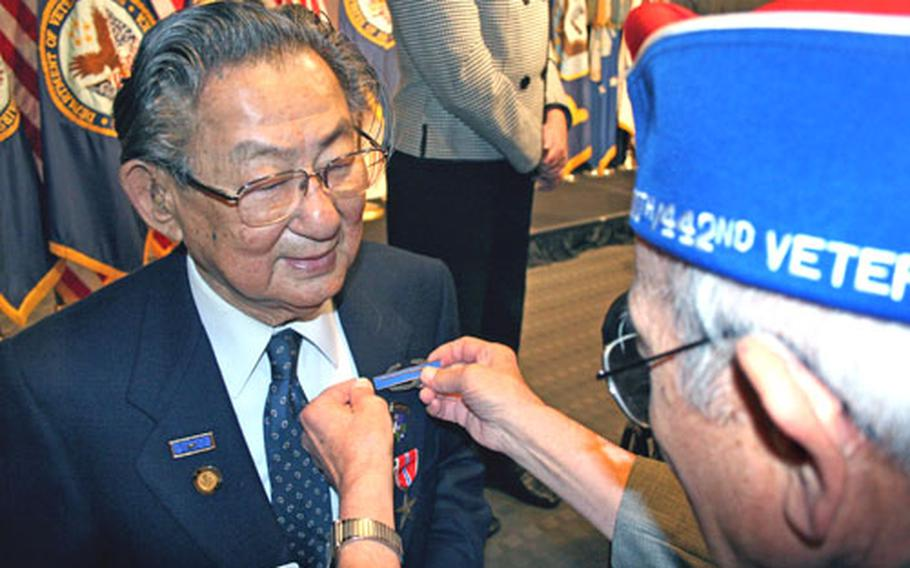 Terry Shima, right, of the Japanese-American Veterans Association helps Ranger Hall of Famer and World War II Merrill's Marauder Grant Hirabayashi pin on his Combat Infantryman Badge before Wednesday's news conference for the Veterans Pride Initiative at the Department of Veterans Affairs building in Washington.