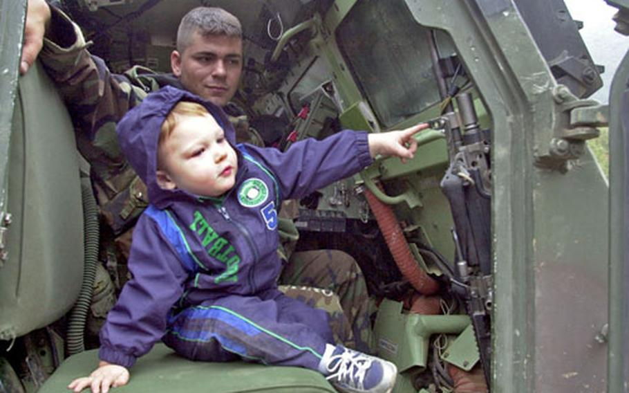 """One-year-old Avin Davis takes a tour of the Multiple Launch Rocket System with Spc. Abram Naber during """"family day"""" for the 2nd Infantry Division's 6th Battalion, 37th Field Artillery at Rocket Valley on Tuesday."""