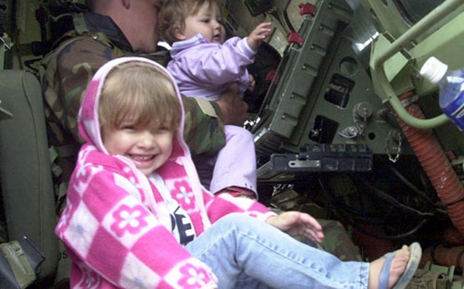 Callie Mack, 3, front, and Hannah Mack, 1, check out the controls of the Multiple Launch Rocket System with Pvt. Chris Trovillo.