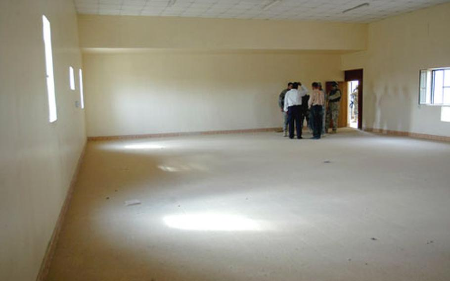 Members of Company B of the 2nd Battalion, 505th Parachute Infantry Regiment, 82nd Airborne Division talk with Wynot city council members Monday in an empty building - constructed with U.S. funds several months ago - intended to be a police station.