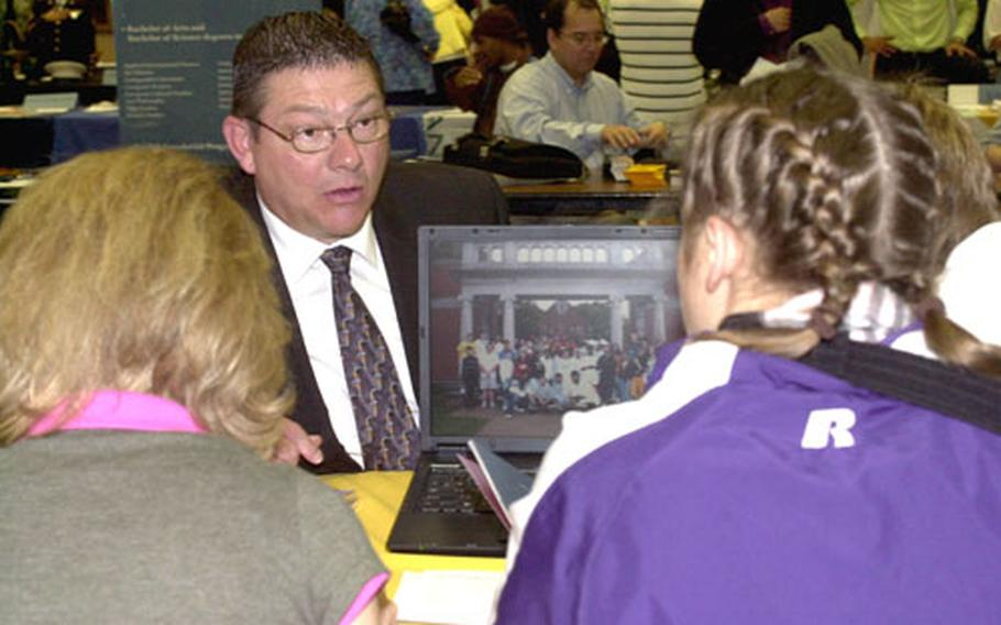 Bob Broshous, center, a representative from the University of Dubuque, talks to prospective college students Thursday.
